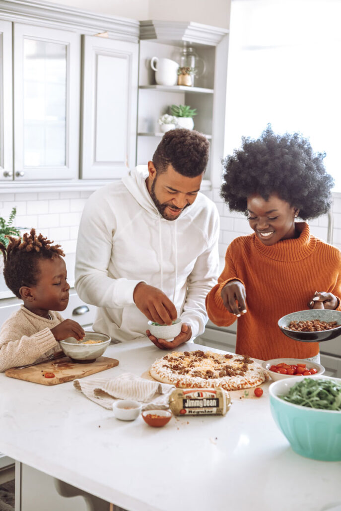 Mom, father and their child making a pizza in a happy family moment